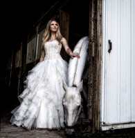 bride in gown stands next to white horse in stable