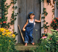 Portrait of young boy leaning on English cottage door holding baseball and bat