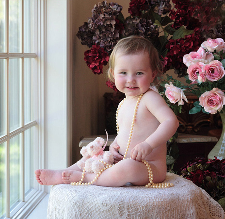 baby girl with pearls smiling for camera in Long Island studio