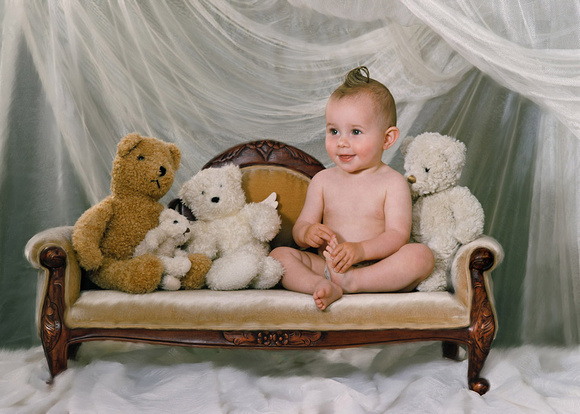 smiling baby boy sits on small gold sofa with teddy bears