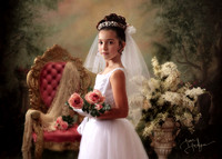 communion girl with roses and vintage pink chair, lace, and urn with white flower arrangement in background at Long Island studio