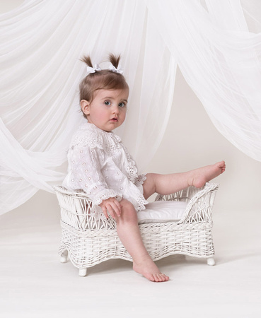 baby in pigtails sitting on wicker stool in white eyelet top