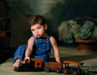 little boy in blue coveralls sitting with wood toy train posing for camera