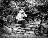 photo of young boy sitting on stone wall with antique bicycle