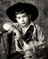 close-up black and white of young boy with cowboy hat and clothing