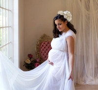 pretty pregnant mom with white draping and hair flowers stands at studio window