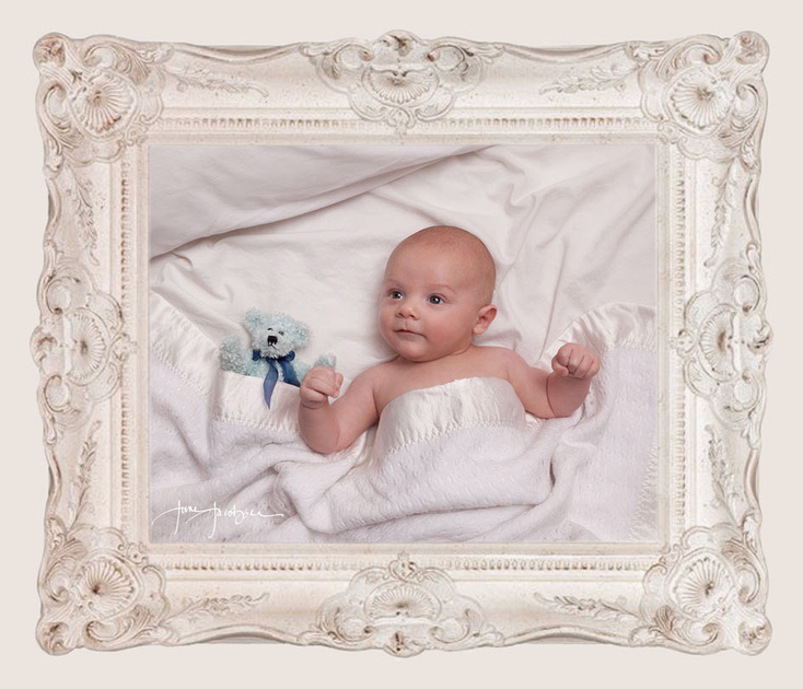 baby boy with teddy bear resting in white sheets on bed in white ornate frame